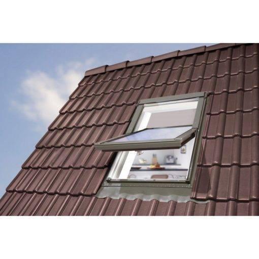 Okno dachowe PVC OptiLight TLP na brązowej dachówce. Popielatoszary kolor zewnętrzny okna dachowego OptiLight TLP pasuje do większości kolorów pokryć dachowych