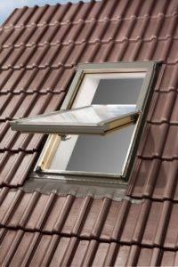 Otwarte okno dachowe OptiLight B na dachu z brązową dachówką