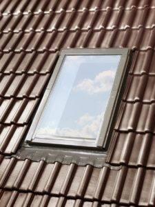 Zamknięte okno dachowe OptiLight B na dachu z brązową dachówką